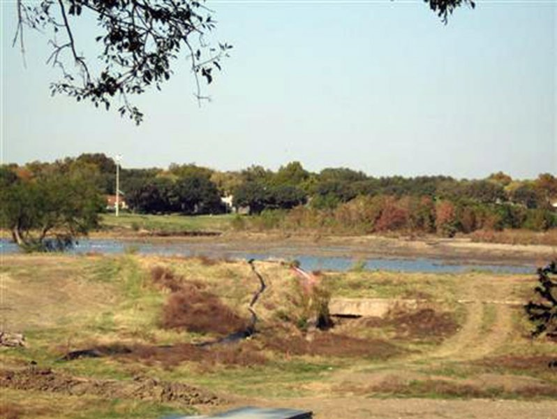 During Dredging - A view of the lake from the south, looking over the long earthen dam. The lake had been drained as part of the dredging operations, but it is partially filled with collected rain water in this picture.