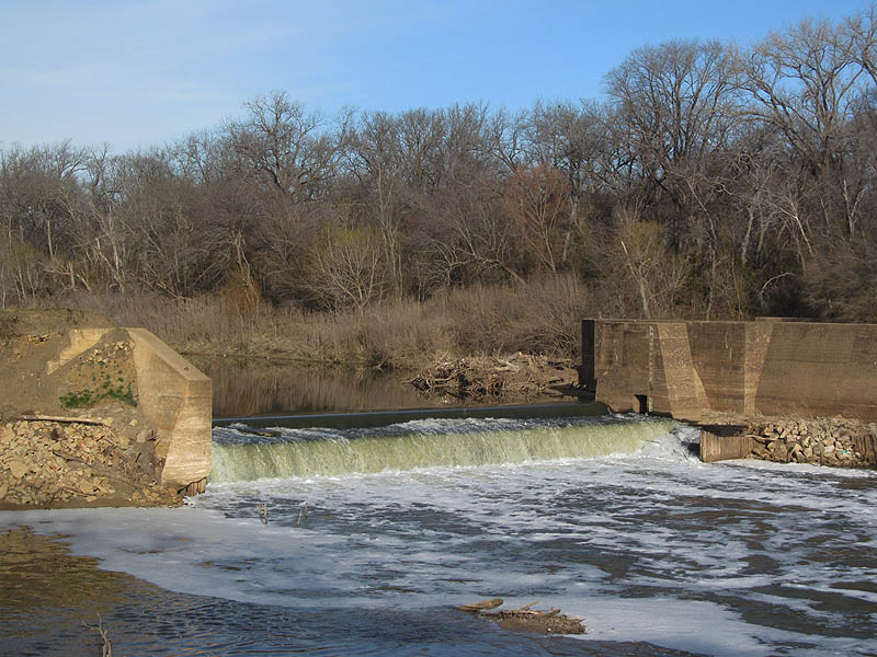 The dam creates a small waterfall on the Trinity River.